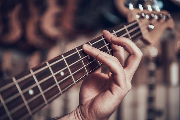 閉じる。男の手がエレキギターのフレットで文字列をクランプします。