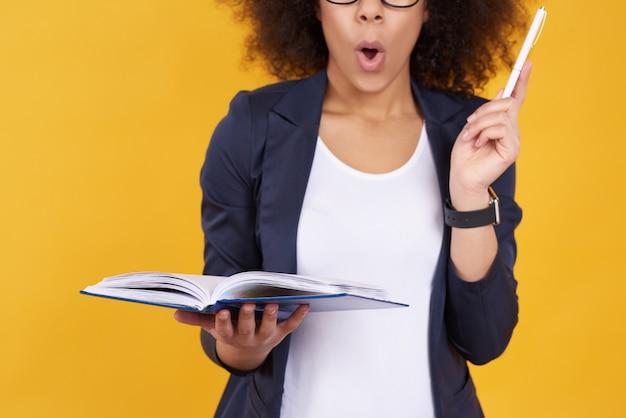 黄色の背景にメモを取っているアフリカ系アメリカ人の女の子。