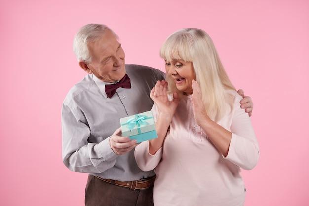 蝶ネクタイの男は、美しい高齢者の女性にギフトボックスをプレゼントします。