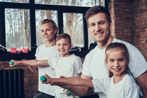 Спортивная семья в белой футболке улыбается и тренируется.
