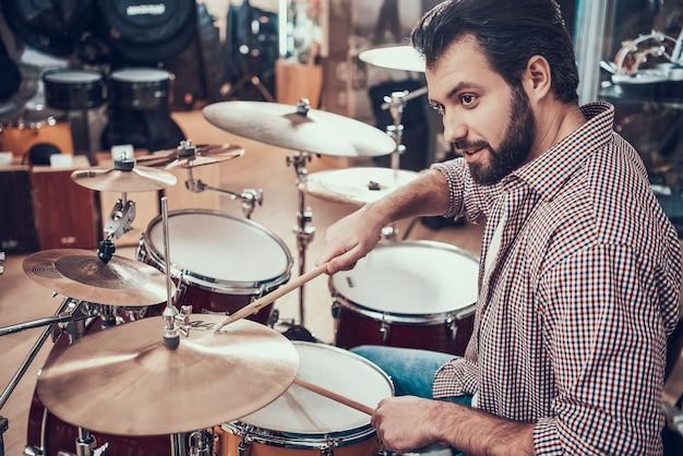 シャツのひげを生やした男はドラムセットを果たしています。