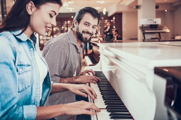 美しい若いカップルが一緒にピアノを弾きます。