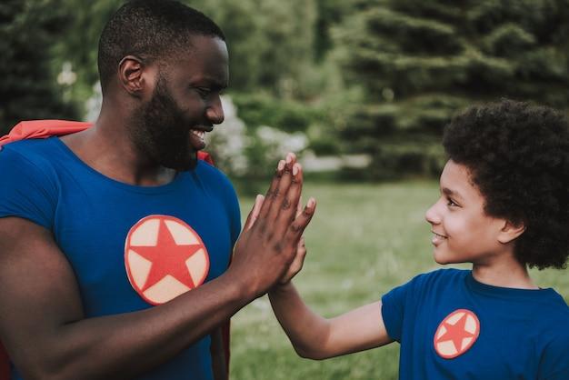 Семья носить костюмы супергероев и дать пять.