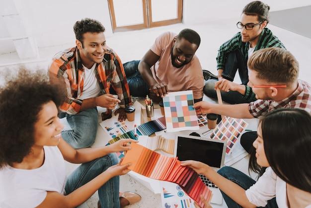 Счастливые молодые люди работают с цветовой палитрой