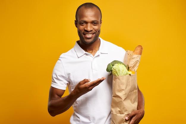 アフリカ人は、新鮮な食材の紙袋を持って立っています。