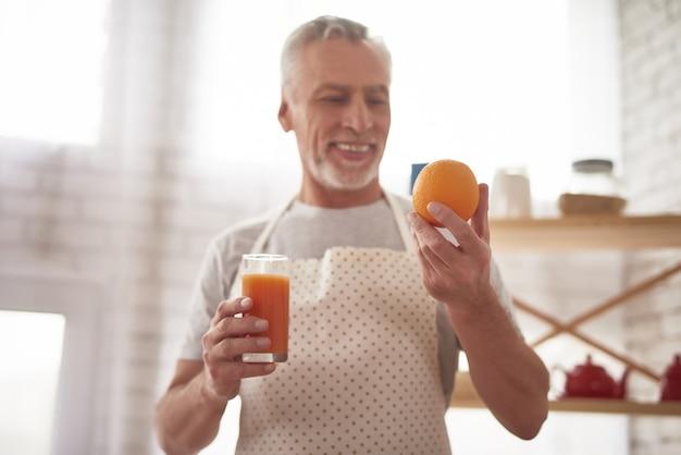 健康的な祖父はガラスのオレンジジュースを得ました。