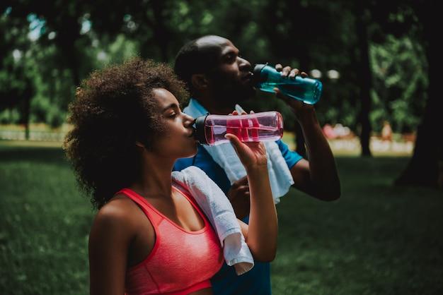 アフリカ系アメリカ人カップルは公園で水を飲む。