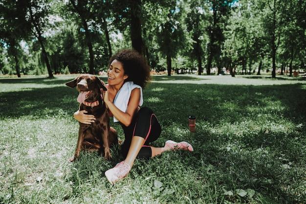 アフリカ系アメリカ人の女性が犬と一緒に座っています。