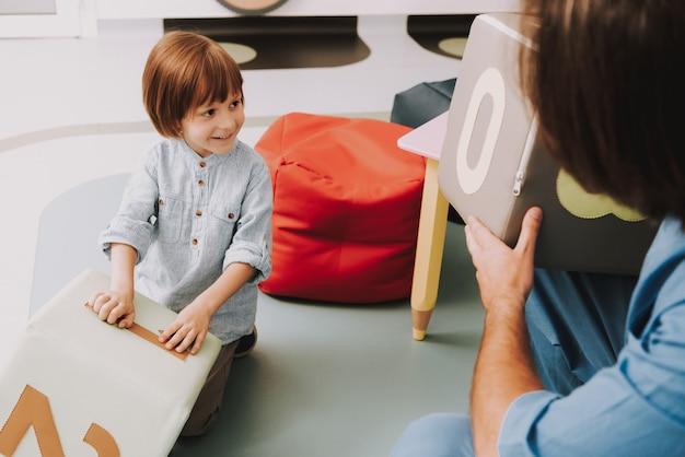 心理学者がオフィスで子供と一緒にブロックをプレイします。