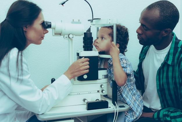 眼科医は、少年患者の目を調べています