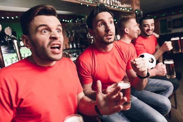 サッカーファンがスポーツバーでゴールを待っています。