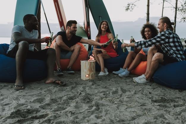 会社は燃えている丸太のまわりの浜で休みます。