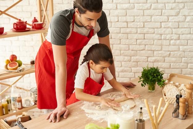 父と娘は生地をロールアウトします。生地麺棒。