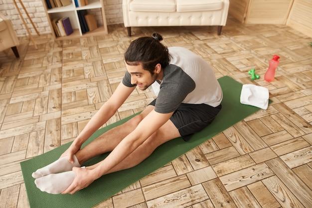 アラブ人はジムのカーペットの上でストレッチ体操をします。