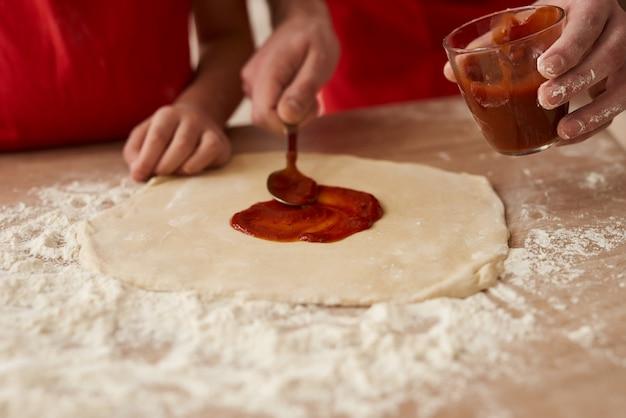 Закрыть пицца готовится с томатным соусом.