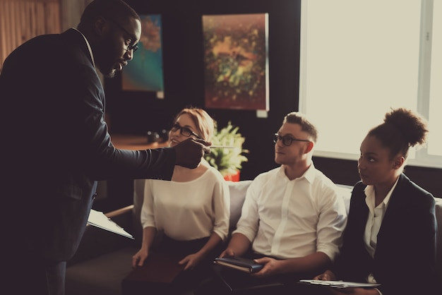アフロアメリカンマネージャーがオフィスでチームビジネスのアイデアを伝えます。