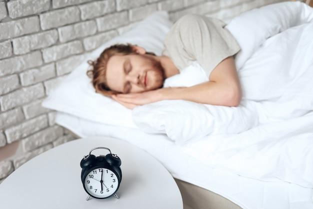 赤い髪の若い男は、時計の近くの寝室で眠ります。