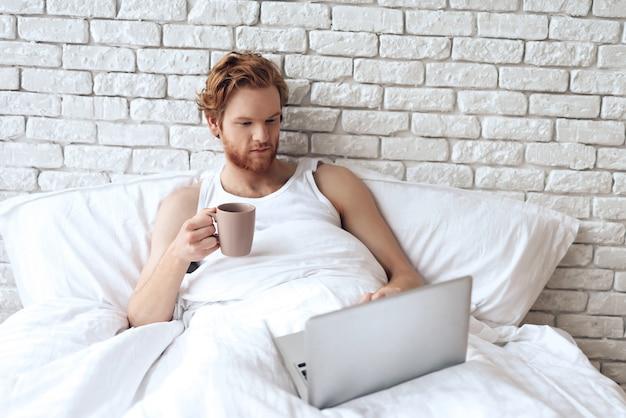 赤い髪の目を覚ます男はノートパソコンと一緒にベッドにあります。