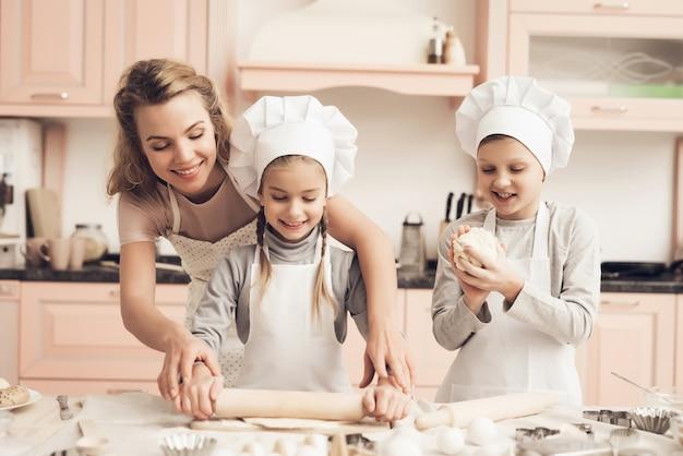 Молодая мама учит маленькую дочь раскатывать тесто.