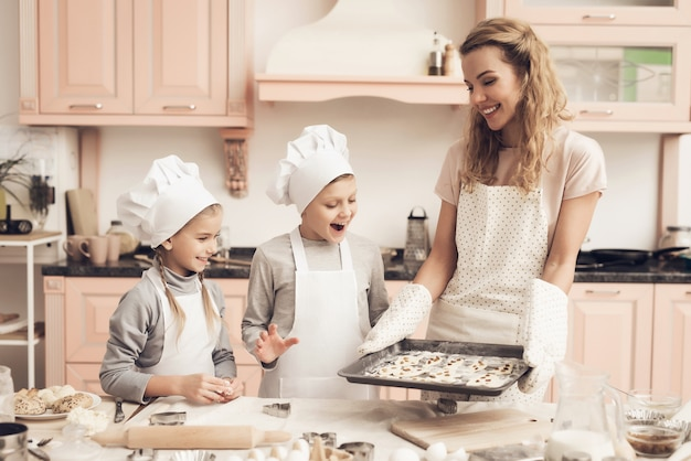 Мама держит сковороду с печеньем счастливые возбужденные дети.
