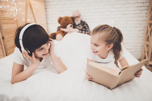 音楽を聴く高活動型の子供たちは夜に読んでいます。