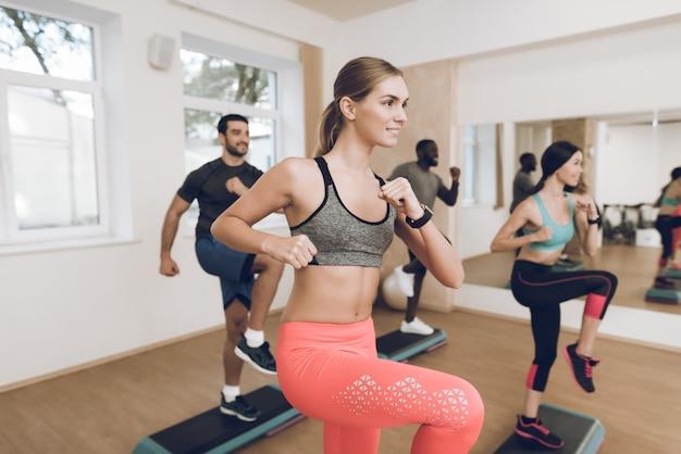 Люди сосредоточены на упражнениях в тренажерном зале.