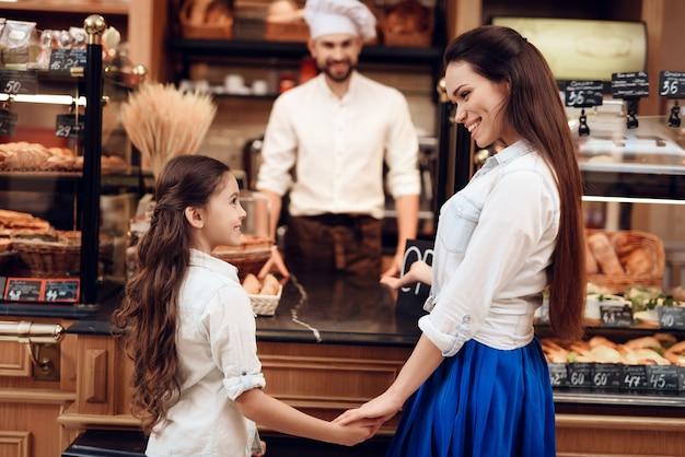 パン屋さんでパンを買う娘を持つ若い女。