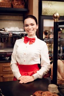 モダンなパン屋さんに立っている若い笑顔の女性。