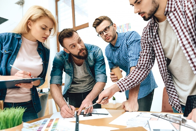 Команда дизайнеров-архитекторов рисует по проекту