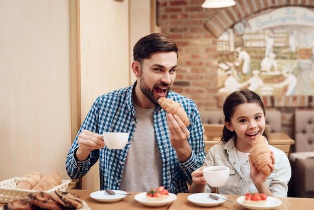 カフェテリアでケーキを食べる娘を持つ父親。