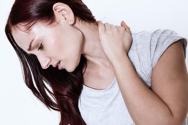 У женщины болит шея в белой комнате.