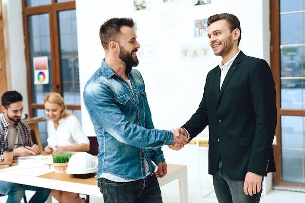 デザイナーと建築家が握手しています。