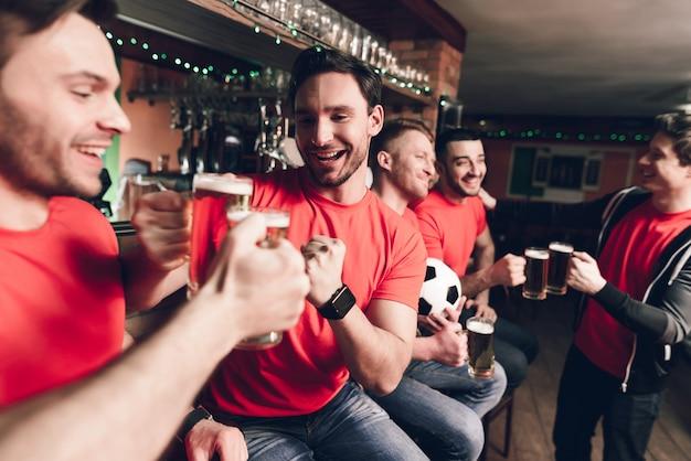 スポーツファンは祝いビールを飲みます。