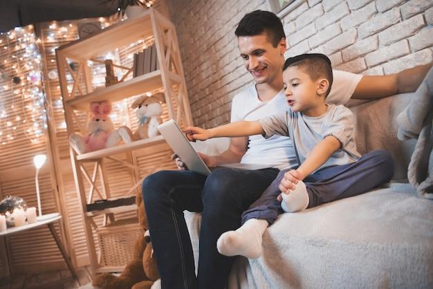 父と幼い息子はラップトップで映画を見ています。