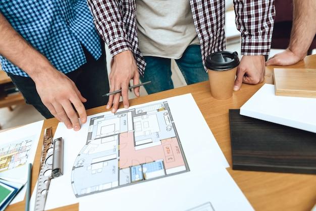 Команда дизайнеров-архитекторов смотрит на планировку этажа.