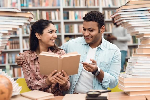 民族のインドの混血少女と男は本を読んでいます。