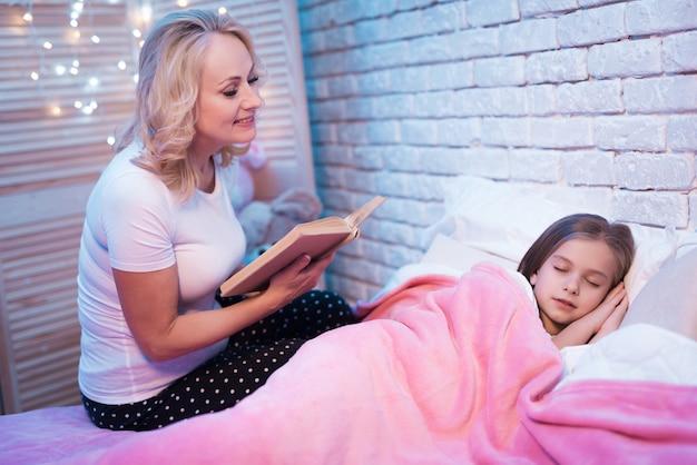 祖母は孫娘が横たわっている間本を読んでいます。