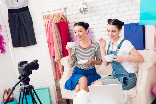 ファッションブロガーの女の子はカメラにお茶を飲みます。