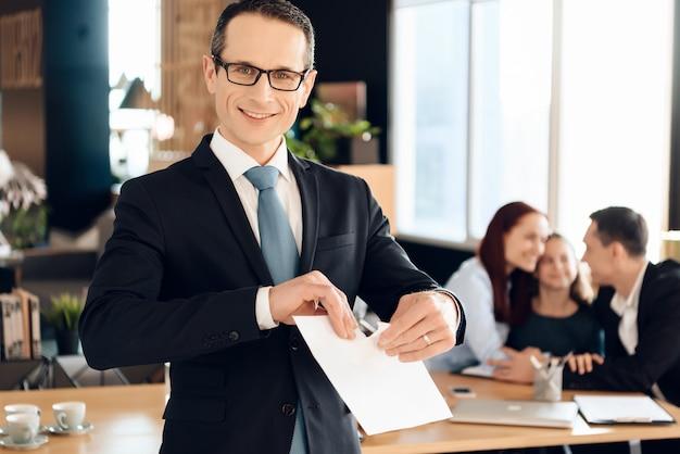 スーツのうれしそうな家族弁護士が紙を引き裂きます。