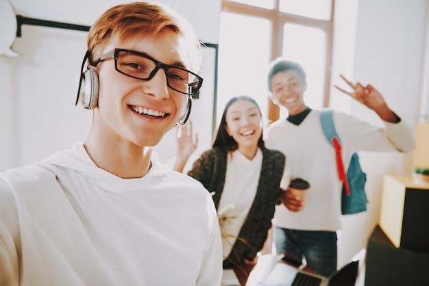 ヘッドフォンで若い男はオフィスで音楽を聴く