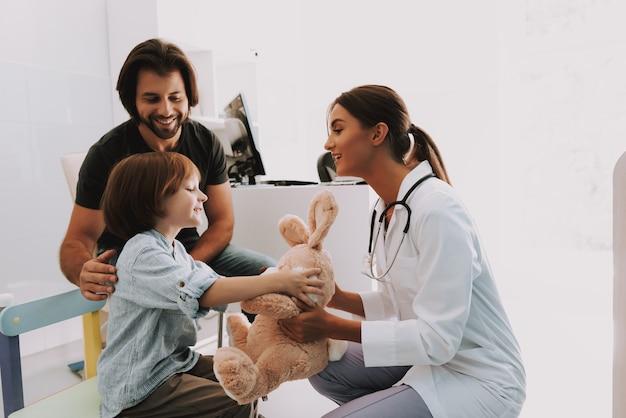 Педиатр женского пола дает ребенку игрушку кролика