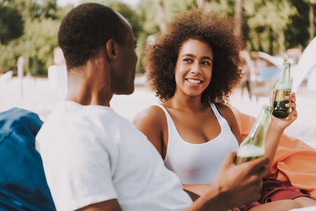 アフリカ系アメリカ人カップルはビーチでビールを飲む