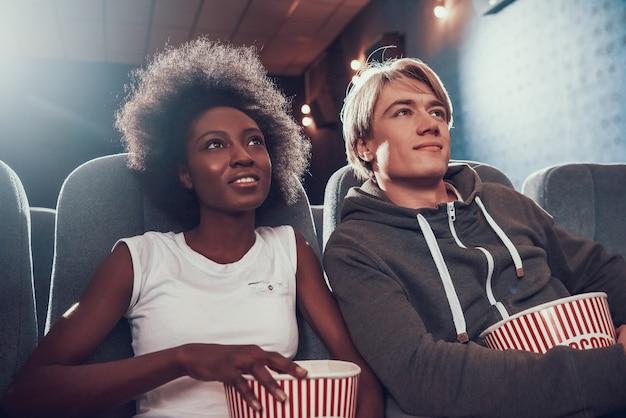 ポップコーンと多国籍カップルは映画館に座っています。