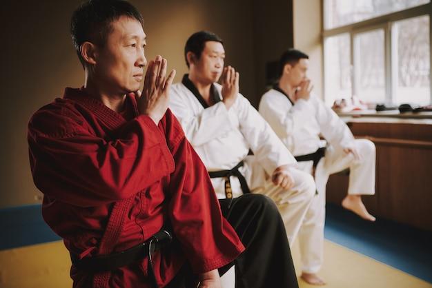 Старший сэнсэй в красных и двух студентов боевых искусств тренируется