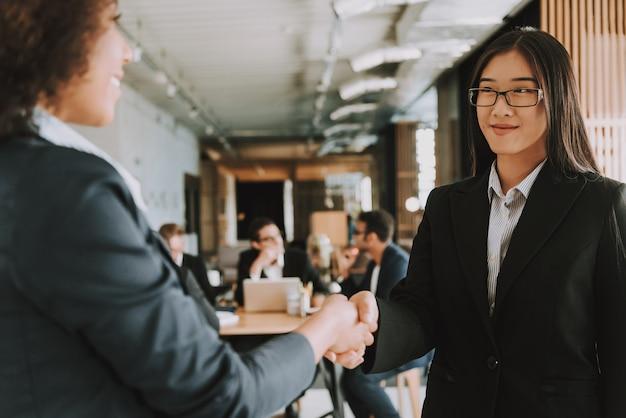 Две молодые деловые женщины пожимают друг другу руки и улыбаются