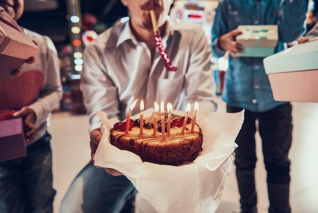 キャンドルで誕生日ケーキを持って男のクローズアップ