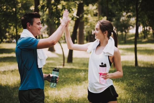 美しい幸せな若いカップルは訓練の後で握手しています