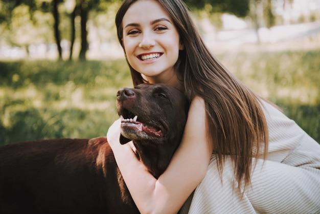 女性が公園で彼女の犬と遊んでいます。