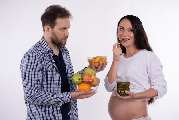 男は白い背景の上の妊娠中の女性に食べ物を提供しています