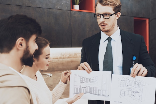 スーツを着た男がカップルのクライアントにキッチンの青写真を見せています。